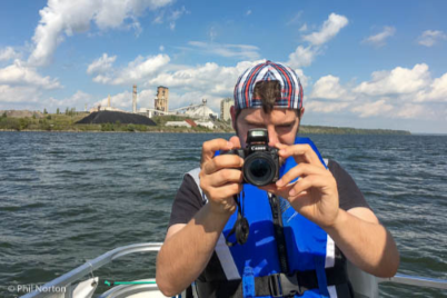person holding a camera on a boat